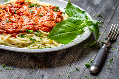 Spaghetti bolognese with seafood and basil. On old wooden table Royalty Free Stock Photo