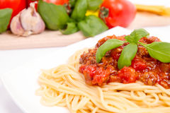 Spaghetti bolognese. Some tomatoes, olive oil, basil, garlic, and raw pasta in the background Stock Photo
