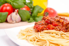 Spaghetti bolognese. Some tomatoes, olive oil, basil, garlic, and raw pasta in the background Stock Photos