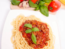 Spaghetti bolognese. Some tomatoes, olive oil, basil, garlic, and raw pasta in the background Royalty Free Stock Photo