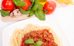 Spaghetti bolognese. Some tomatoes, olive oil, basil, garlic, and raw pasta in the background Stock Photography