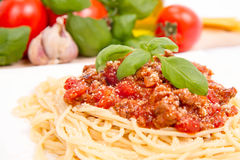 Spaghetti bolognese. Some tomatoes, olive oil, basil, garlic, and raw pasta in the background Royalty Free Stock Images
