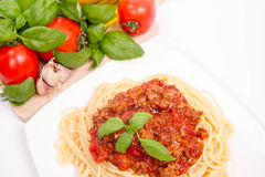 Spaghetti bolognese. Some tomatoes, olive oil, basil, garlic, and raw pasta in the background Royalty Free Stock Photography