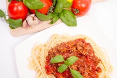Spaghetti bolognese. Some tomatoes, olive oil, basil, garlic, and raw pasta in the background Stock Image