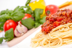 Spaghetti bolognese. Some tomatoes, olive oil, basil, garlic, and raw pasta in the background Royalty Free Stock Image