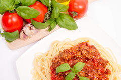 Spaghetti bolognese. Some tomatoes, olive oil, basil, garlic, and raw pasta in the background Stock Images