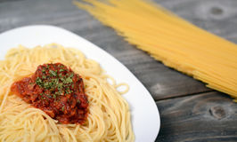 Spaghetti bolognese with  tomato beef sauce and raw pasta in bac Royalty Free Stock Photos