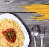 Spaghetti bolognese with  tomato beef sauce and raw pasta on woo Stock Photography