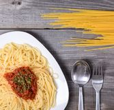 Spaghetti bolognese with  tomato beef sauce and raw pasta on wooden background royalty free stock photography