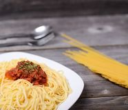 Spaghetti bolognese with  tomato beef sauce and raw pasta on wooden background stock photo