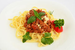 Spaghetti Bolognese on white plate close up. Spaghetti Bolognese with fresh herb spices - oregano, basil, rosemary, celery and red pepper, served on white Royalty Free Stock Photography
