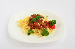 Spaghetti Bolognese on white plate. Spaghetti Bolognese with fresh herb spices - oregano, basil, rosemary, celery and red pepper, served on white ceramic plate Royalty Free Stock Photo