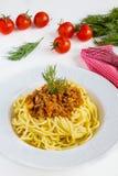 Spaghetti bolognese on white plate. On white table Royalty Free Stock Photo