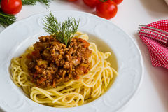 Spaghetti bolognese on white plate. On white table Stock Photography