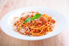Spaghetti bolognese on white plate with tomato sauce and basil Royalty Free Stock Images