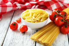 Spaghetti with bowl of pasta and tomatoes on a white wooden background Royalty Free Stock Photos