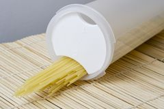 Spaghetti In a box. Uncooked spaghetti pasta being poured out of a clear plastic box Royalty Free Stock Photo