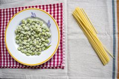 Spaghetti with broad beans. Dish of broad beans with near some raw spaghetti pasta royalty free stock photo
