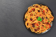 Spaghetti with capers. olives, anchovies, tomato sauce. Delicious Spaghetti alla puttanesca with capers. olives, anchovies, tomato sauce sprinkled with parsley Stock Images