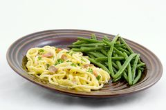 Spaghetti carbonara. Made with ham instead of bacon, add bits of parsley and diced tomatoes for color. French green beans with dill seasoning make up the side royalty free stock photo