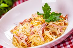 Spaghetti Carbonara with bacon, yolk and cheese on white plate. Close up stock images