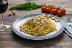 Spaghetti Carbonara con il prosciutto ed i funghi in piatto blu sulla tavola di legno immagine stock