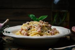 Spaghetti Carbonara Carbonara d'alla de pâtes avec de la sauce crème, un lard et un poivre d'un plat blanc photographie stock libre de droits