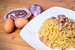 Spaghetti carbonara. Delicious spaghetti with bacon and egg called alla carbonara on wooden table Royalty Free Stock Image