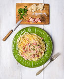 Spaghetti carbonara in green plate on white wooden background Royalty Free Stock Photos