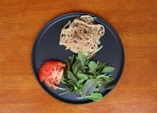 The Spaghetti Carbonara with green vegetable and red tomatoes cut into pieces in the black dish. stock images