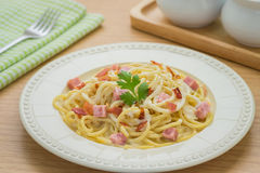 Spaghetti carbonara with ham and bacon on plate Stock Images