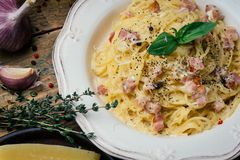 Spaghetti Carbonara. Pasta alla carbonara with a cream sauce, bacon and pepper on a white plate. stock photo