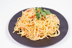 Spaghetti Carbonara. With some parsley on a black plate on a white background royalty free stock photo