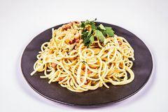Spaghetti Carbonara. With some parsley on a black plate on a white background royalty free stock photos