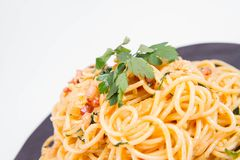 Spaghetti Carbonara. With some parsley on a black plate on a white background stock image