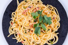 Spaghetti Carbonara. With some parsley on a black plate on a white background royalty free stock images
