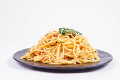 Spaghetti Carbonara. With some parsley on a black plate on a white background stock images