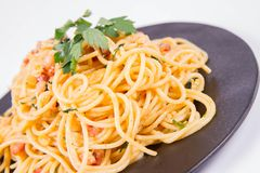 Spaghetti Carbonara. With some parsley on a black plate on a white background stock photos
