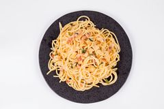 Spaghetti Carbonara. With some parsley on a black plate on a white background stock photo