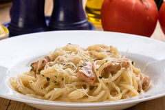 Spaghetti carbonara on wooden table Stock Photos