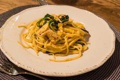 Spaghetti casalinghi con gli spinaci ed il pollo del bambino alla Tabella di cena con bicchiere di vino fotografia stock