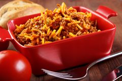 Spaghetti casserole. Homemade food , served from small red ceramic oven pan Stock Photo