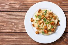 Spaghetti with chanterelles mushrooms top view. Pasta spaghetti with chanterelles mushrooms on a wooden background top view royalty free stock images