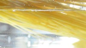 Spaghetti che cadono nell'acqua stock footage