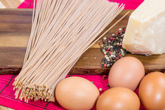Spaghetti with cheese, garlic and eggs on a wooden board Royalty Free Stock Image