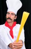 Spaghetti and Chef. Serious chef holding spaghetti and ready to fight Stock Photo