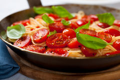Spaghetti with cherry tomato on a rustic pan Royalty Free Stock Images