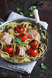 Spaghetti with cherry tomatoes, bacon slices and capers Stock Photography