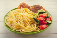 Traditional dish consisting of spaghetti with chicken cutlets and vegetable salad. stock images