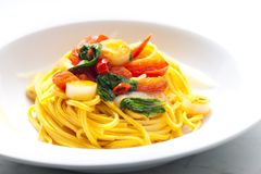 Spaghetti with chilli tomatoes and spinach. Close, closeup, cooked, cuisine, dish, food, gastronomy, indoor, nourishment, nutrition, plate, pasta, italy stock photo